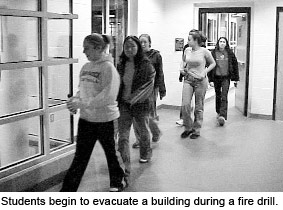 Students begin to evacuate a building during a fire drill.